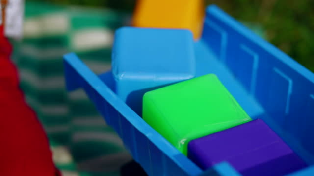 Little boy plays with cubes and machine in the garden video