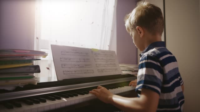 vídeos de stock e filmes b-roll de little boy practicing digital piano in 4k - piano