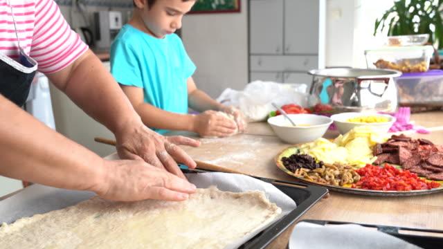 vidéos et rushes de petit garçon préparant la pizza avec sa grand-mère dans la cuisine - recette