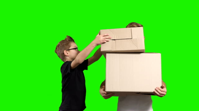 Little boy puts boxes one by one in brother's hands video