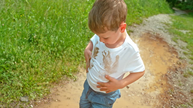 SLO MO Little boy putting his hands in the muddy puddle and wiping them in his clean white t shirt