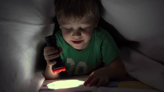 little boy reading a book at night under a blanket with a flashlight