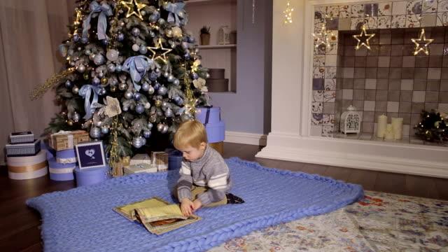 Little boy reading a book near Christmas tree. video