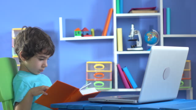 Little Boy Reading Book And Using Notebook Computer video