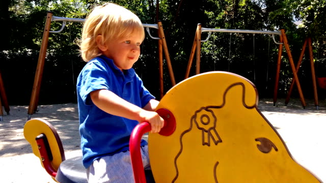 Little boy ridding a toy horse Little boy ridding a toy horse outdoor play equipment stock videos & royalty-free footage
