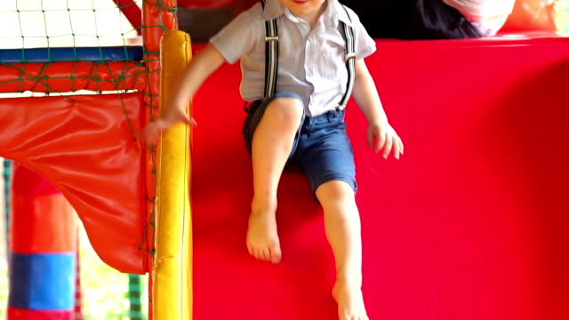 Little boy ride a plastic slide on the playground. video