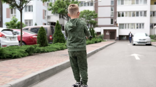 A little boy rides a scooter near the park in quarantine. The concept of COVID-19 infection and self-isolation of children during quarantine. video