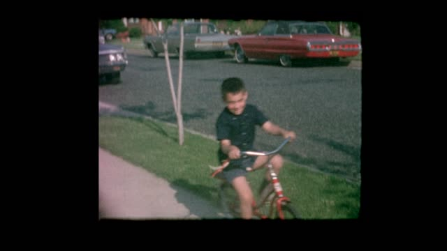 1964 男の子郊外の路上ビンテージ車の横に自転車に乗る - 郷愁点の映像素材/bロール