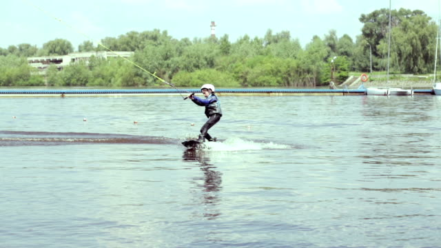 Little boy riding a wakeboard in the park video