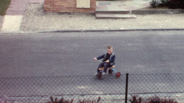 Little boy riding trike on street (vintage 8mm film) video