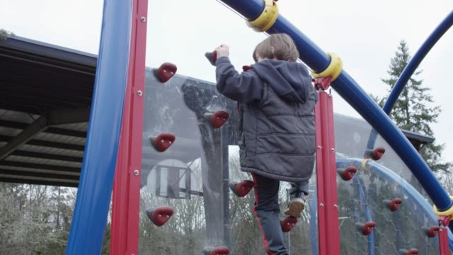 Little Boy Rock Climbing in Playground video