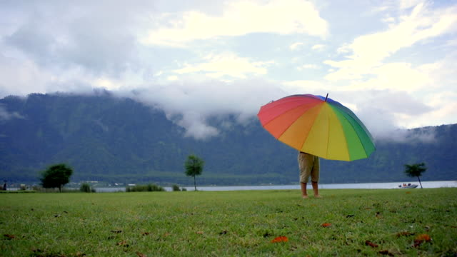 Little boy rotates the umbrella on the Bratan lake video