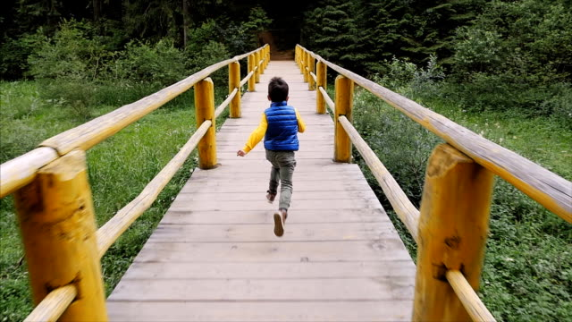 Little boy running acroos the bridge