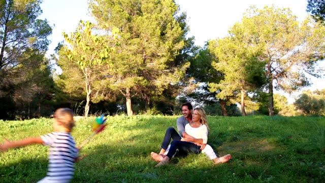 little boy running around his parents in the park video