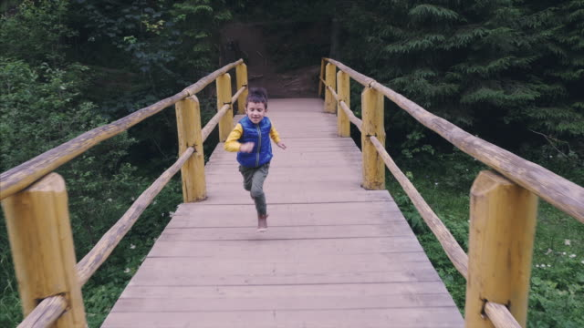 Little boy running at hight pace acroos the bridge
