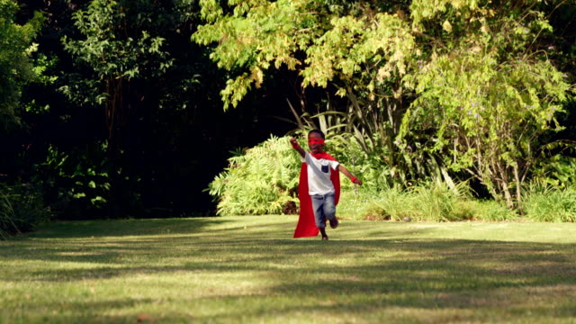 Little boy running in costume of superhero video