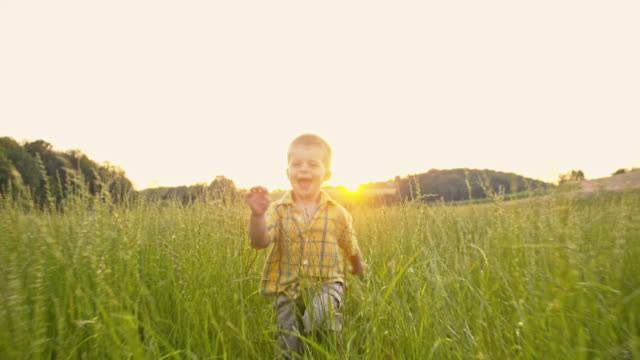 SLO MO Little boy running in the high grass video