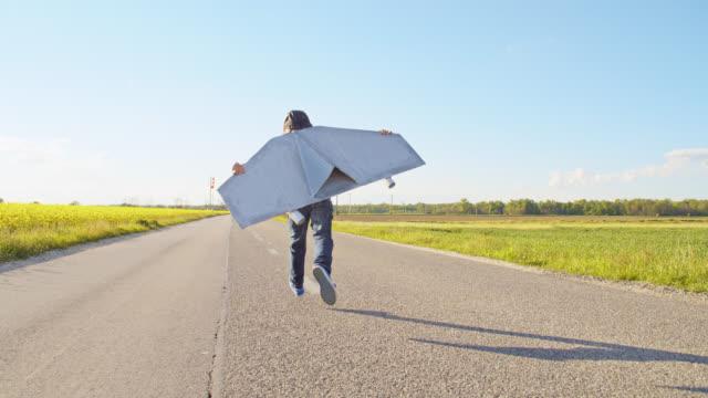 slo mo little boy running on a country road in a jet pack costume - skrzydło samolotu filmów i materiałów b-roll