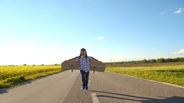 SLO MO Little boy running on a country road in an airplane costume video