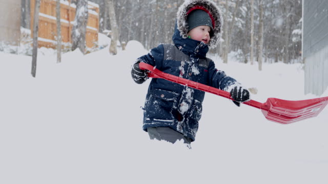 Little Boy Shoveling Snow After Winter Storm.