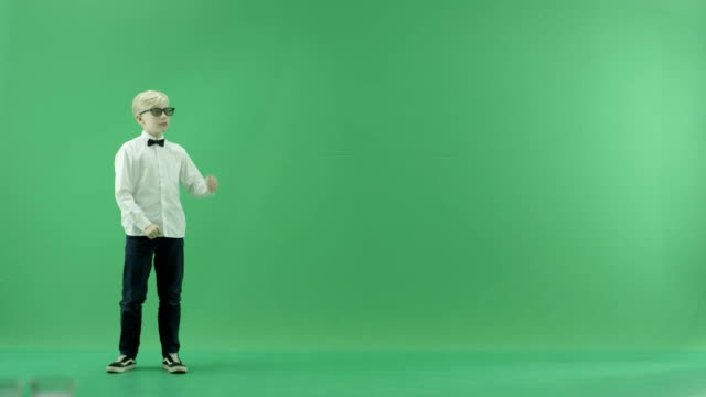 vídeos de stock e filmes b-roll de little boy showing the forecast of hot and rainy weather on the left side on the green screen - weatherman