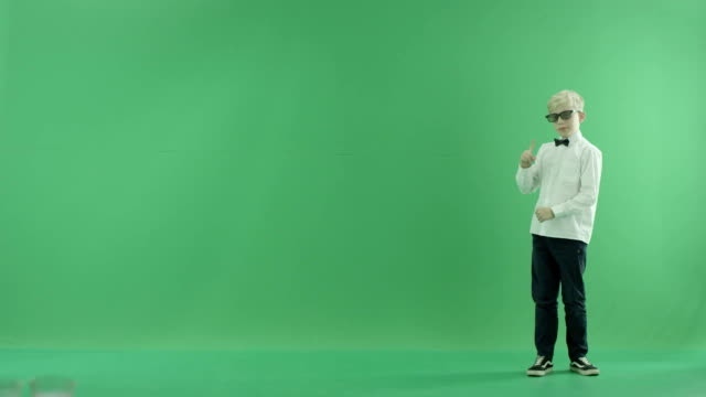vídeos de stock e filmes b-roll de little boy showing the forecast of hot and rainy weather on the right side on the green screen - weatherman