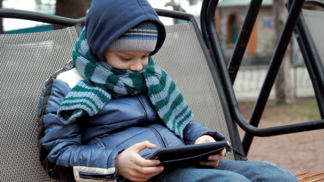 little boy sitting alone on swing with digital tablet video