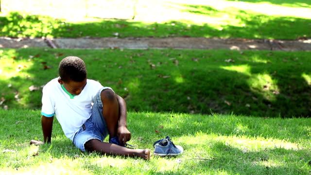 ragazzino seduto sull'erba togliere le scarpe - 8 9 anni video stock e b–roll