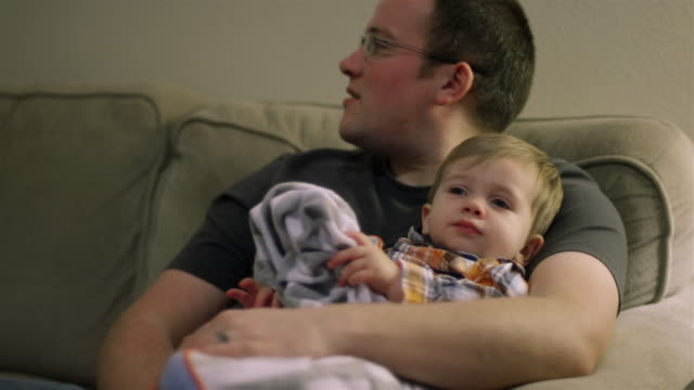 Little boy sitting on his dad's lap and looking tired video