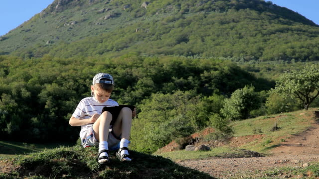 little boy sitting, reading e-reader on walk in mountain video