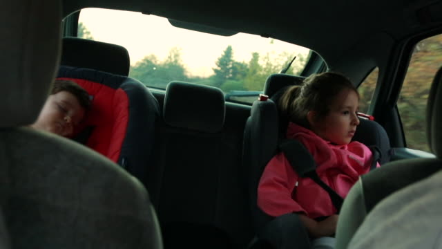 Little boy sleeping in car safety seat while sister trying to have a nap on a road trip