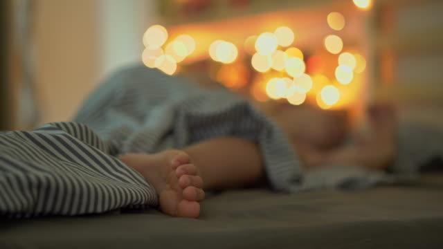 vidéos et rushes de un petit garçon dormant dans son lit avec un calendrier de l'avent s'éclaircit avec des lumières de noel brille sur un dos de son lit. se préparer pour le concept de noel et du nouvel an. concept de calendrier de l'avent - calendrier de l'avent
