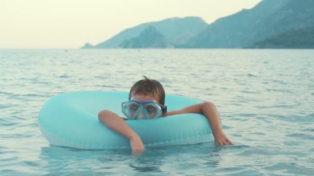 liten pojke sova på gummiringen simning i havet. barn avkopplande till sjöss - inflatable ring bildbanksvideor och videomaterial från bakom kulisserna