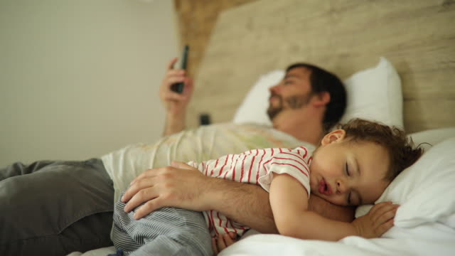 Little boy sleeping while his father using smart phone in bed