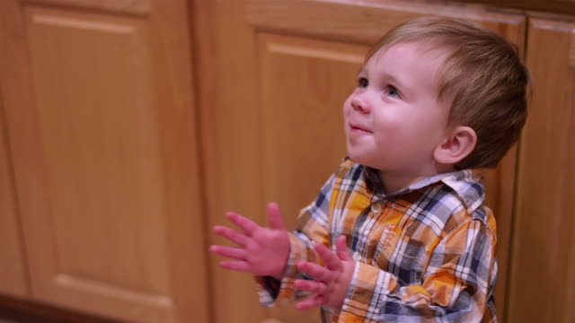 Little boy smiling and clapping in a kitchen, and being fed a spoonful of food video
