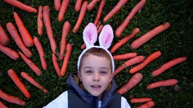 kleiner junge lächelt und grimmig, während er sich in einem feld von karotten ausruht - karotte peace stock-videos und b-roll-filmmaterial