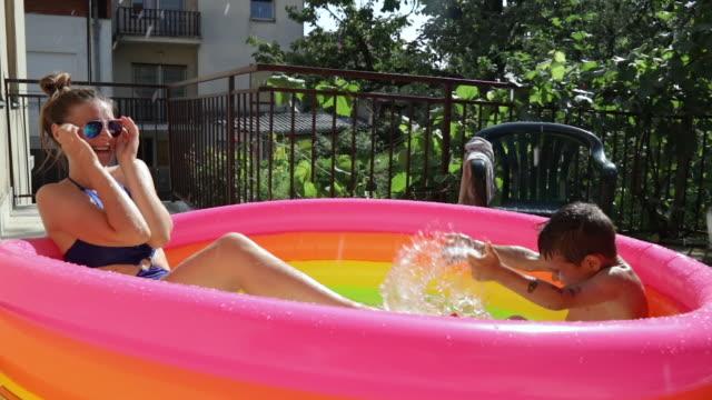 vídeos y material grabado en eventos de stock de niño salpicando agua en la cara de su hermana en piscina inflable - backyard pool