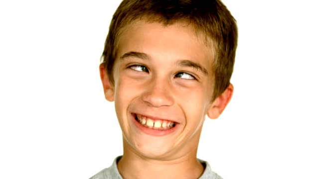 Little boy squinting against white background video