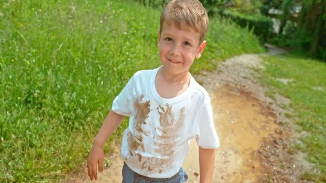 SLO MO Little boy standing in the puddle with a dirty white t shirt smiling into the camera