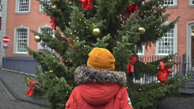 Little boy  standing near Christmas tree in Monschau Little  Caucasian boy standing near Christmas tree in Mounschau in winter christmas fun stock videos & royalty-free footage