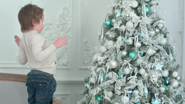 Little boy sticking his tongue out at his own reflection in the bauble on the Christmas tree video