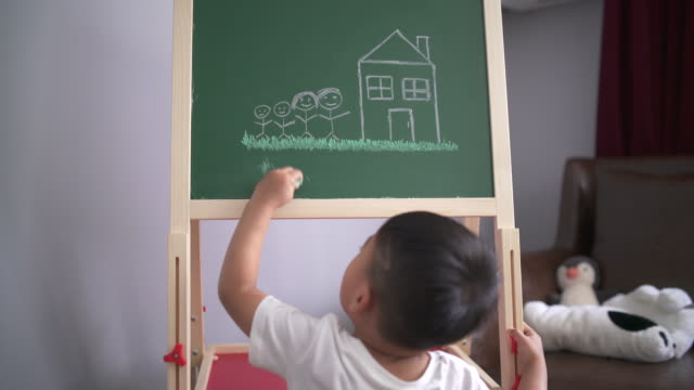 Little boy struggling to draw on his chalkboard Little boy too short to reach his chalkboard. short length stock videos & royalty-free footage