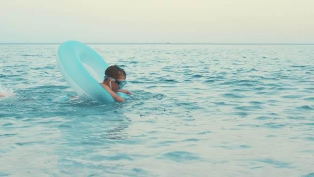 liten pojke simning på uppblåsbara cirkel till sjöss. kid slår vatten med fötter - inflatable ring bildbanksvideor och videomaterial från bakom kulisserna