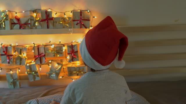 der kleine junge nimmt ein geschenk aus einem adventskalender, der an einem bett hängt, das mit weihnachtsbeleuchtung aufgehellt ist. vorbereitung auf weihnachten und neujahr konzept. adventskalenderkonzept - advent stock-videos und b-roll-filmmaterial