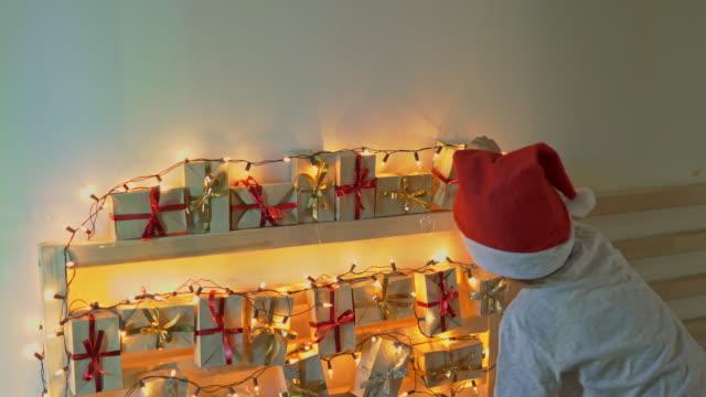 vidéos et rushes de petit garçon prend un cadeau d'un calendrier de l'avent accroché à un lit qui est allégé avec des lumières de noel. se préparer pour le concept de noel et du nouvel an. concept de calendrier de l'avent - calendrier de l'avent