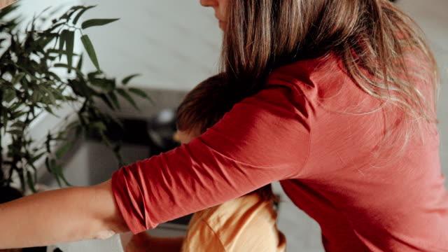stockvideo's en b-roll-footage met kleine jongen nemen van papieren handdoek te blazen zijn neus terwijl moeder voor te bereiden ontbijt op de achtergrond - oil kitchen
