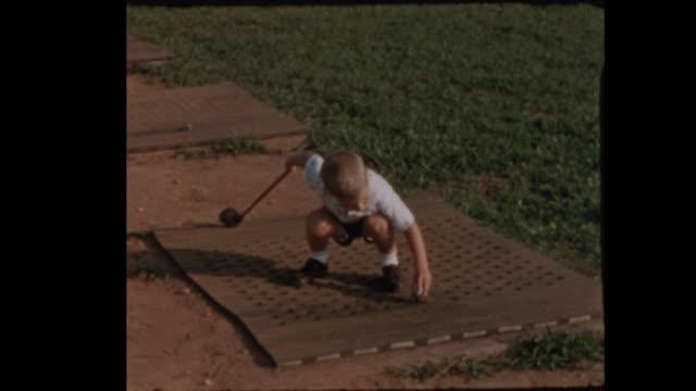 Little boy tees off at Golf Driving Range