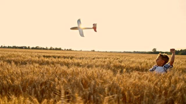 slo mo 少年投げる飛行機トーイ - 男の子点の映像素材/bロール