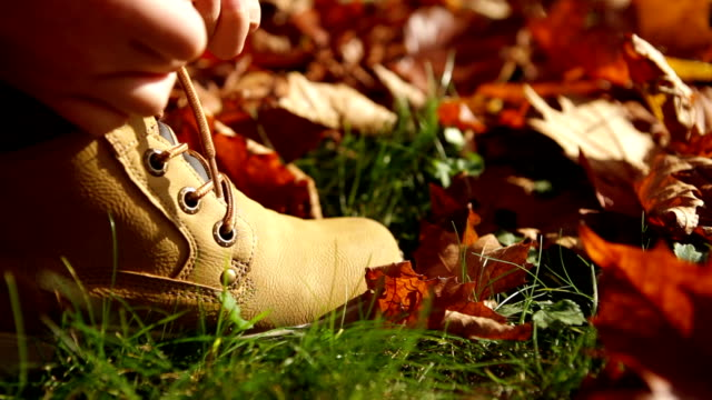 Little boy ties the boots laces during sunny autumn day outdoor walking and ant crawling on the boot video