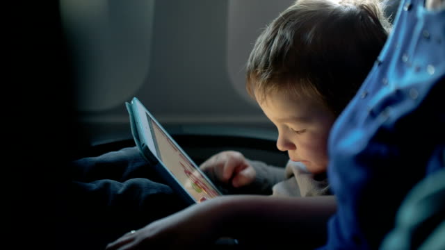 Little boy traveling in an airplane Little boy traveling in an airplane sitting in his seat playing with a tablet computer watched by a parent arts culture and entertainment stock videos & royalty-free footage